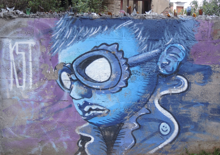 mural of a boy's head in profile, short hair, wearing goggles, all in blue shades