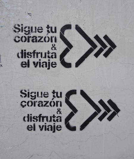 black stencil on grey concrete, sigue tu corazon a disfruta la viaje, written twice