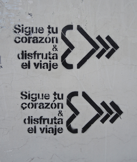 black stencil on grey concrete, sigue tu corazon a disfruta la viaje, written twice