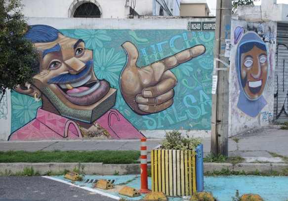 large man's face with laughing open mouth, moustache and short hair, pink shirt collar, hand with index finger pointing , mural in Quito Ecuador , Hecho salsa