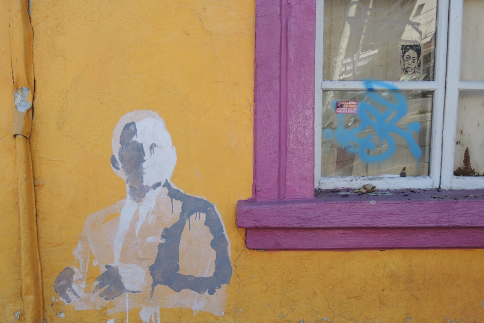 grey and white painted stencil of a man including head, upper body and one arm. on a yellow wall beside a window with a pink window frame. There is a sticker or pasteup of another face in the window looking out.