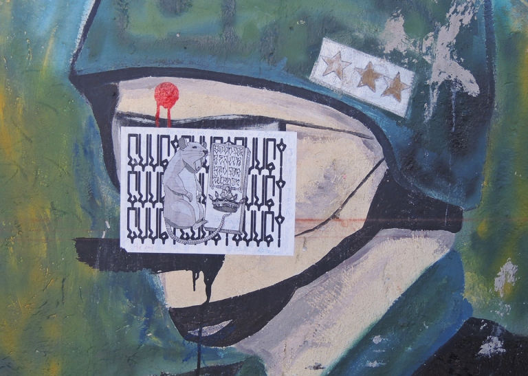 part of a larger mural with soldier, wearing helmet with three gold stars on it, someone has put a red dot in the middle of his forehead, also a pasteup now covers his face, with a rat on it, mural in Quito Ecuador