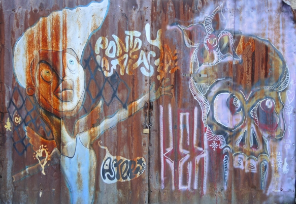 on a rusted metal gate that is locked closed, graffiti of a person with outstretched arm, as well as a skull