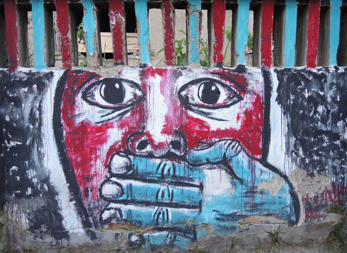 mural in Quito Ecuador , large red face with a blue hand covering its mouth