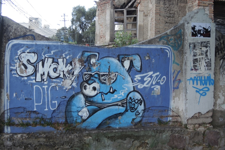 painted in blue, a pig with sunglasses and crossed arms, words say smoky pig