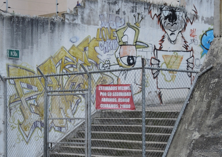 graffiti on a wall beside an outdoor stairwell, behind a chainlink fence in Quito Ecuador