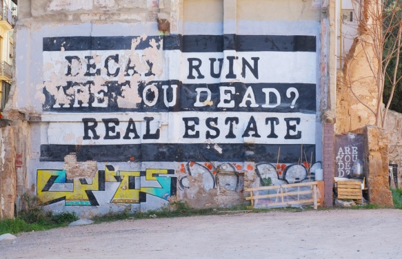 large street art painting in black and white, on the side of a building, as seen from across a vacant lot. Words say Decay Ruin Are you dead? Real Estate
