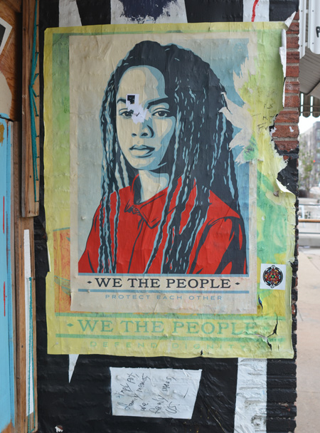 we the people poster featuring a young black woman with long dreadlocks and a red t-shirt