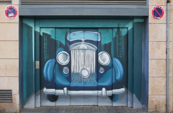 blue car, vintage, large round headlights, front view, painted on a garage door.