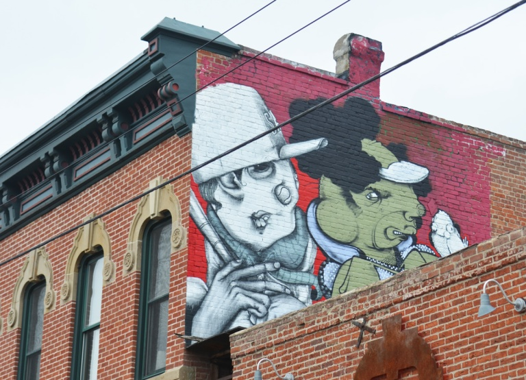 a mural on an upper level of a building, two characters, one white and one green,