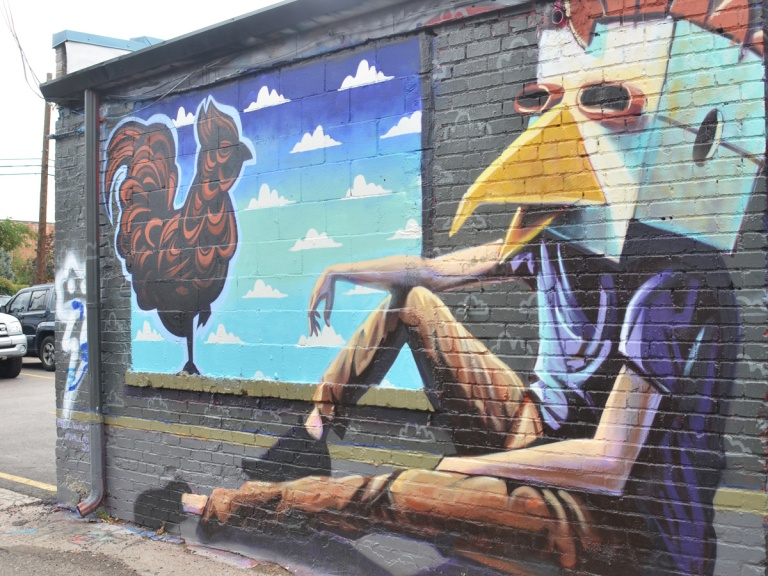 mural of a chicken standing in a window. sitting on the ground beside the window is a young man in brown pants and blue t-shirt with a chicken mask covering his face