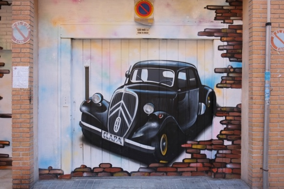 street art of an old car painted on a garage door - black car from the 1930s or 1940s