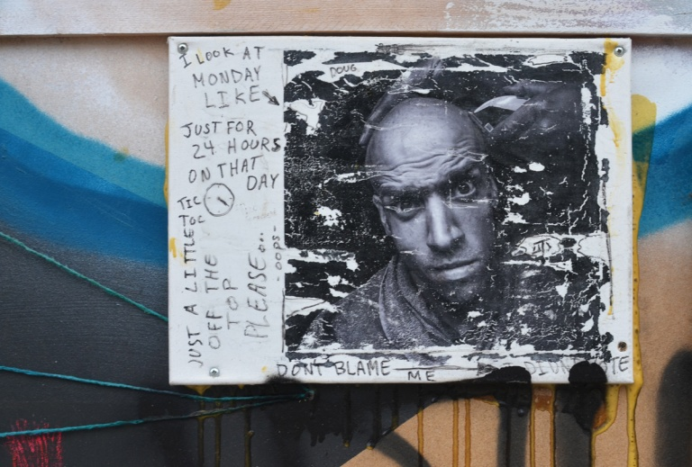 picture of a man in black and white, mount on a wall, weathered, some writing around the edges