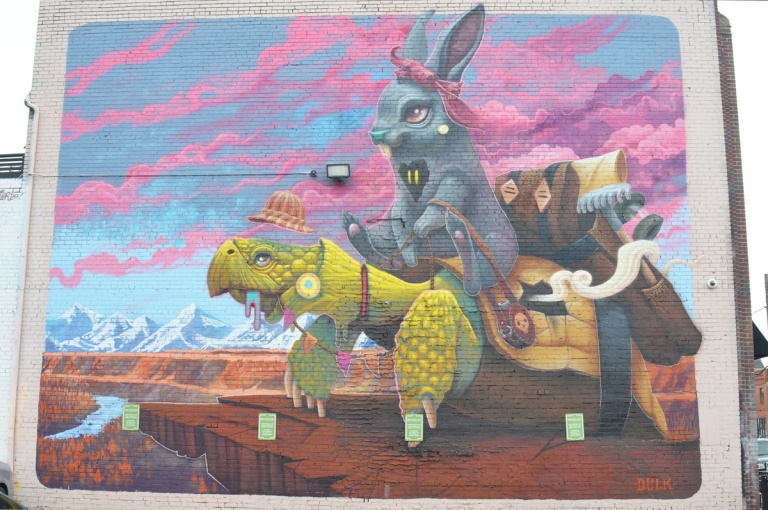 a large mural of a grey rabbit sitting on a green turtle