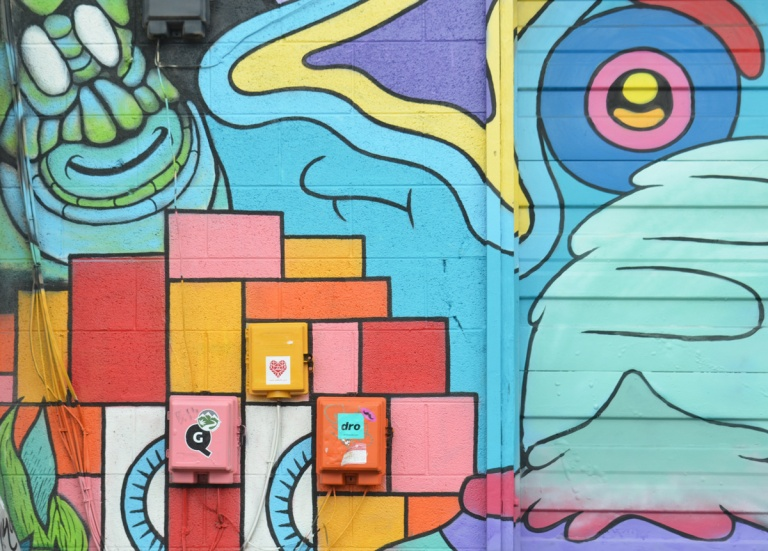 mural in bright colours and abstract shapes, one wringly face, an eye and a nose, some squares,