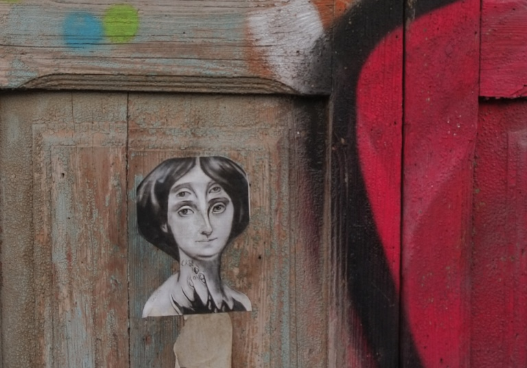 black and white paste up by CKTN on a wooden door of a woman's head, she has 4 eyes,