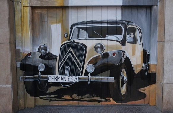 street art of an old car painted on a garage door - licence plate says germanies 8