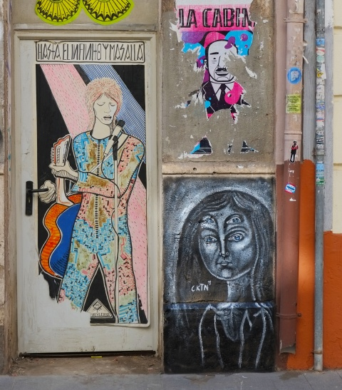 two pasteups on a wall, one is a tribute to david bowie that says hasta el infinito mas ala which means to inifite and beyond