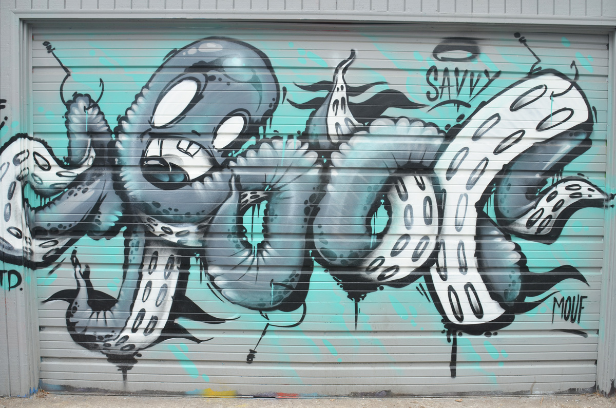 mural on a garage door of a large octopus with its legs all tied up in knots.