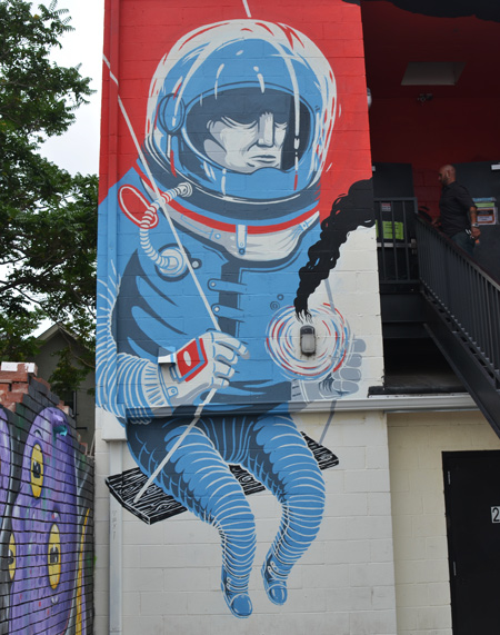 an astronaut dressed in blue sitting on a kids swing, mural, two storeys high, helmet,