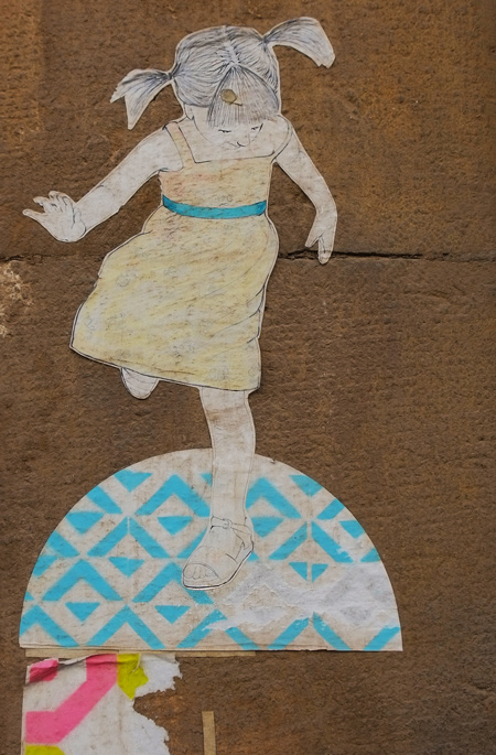 small paper pasteup in pastel colours of a young girl in pigtails hopping on a blue and white semi circle