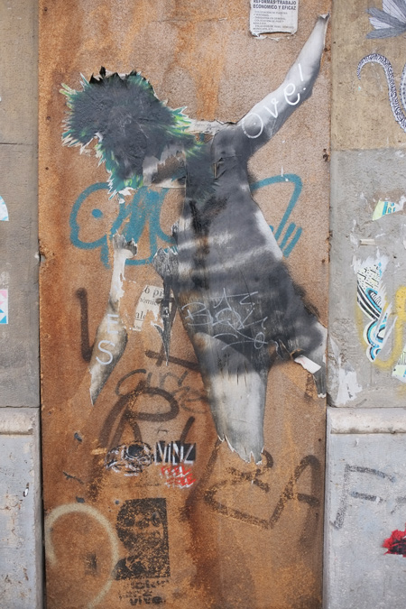 damaged pasteup of the back of a woman in short skirt and shoulder length hair.