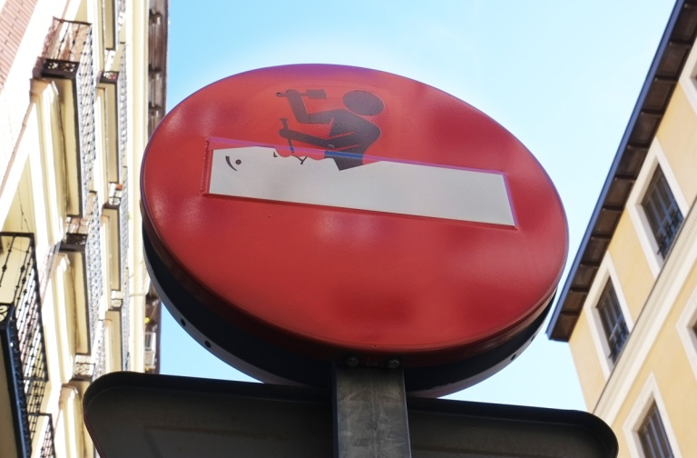 altered do not enter sign,man chiseling out a face from stone, white bar as the block of stone