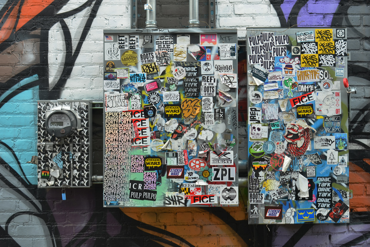 two metal boxes outside and a meter box, all covered with stickers