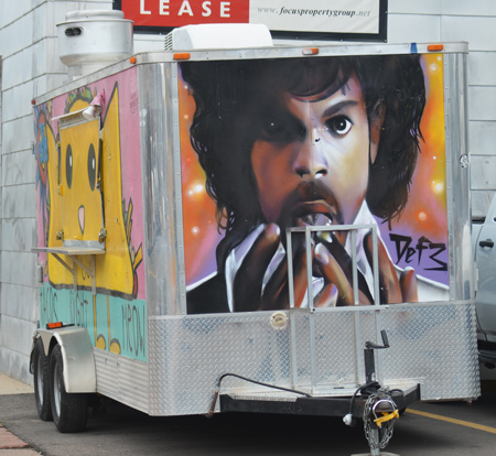 a metal enclosed trailer is in a parking lot, the back has a portrait of Prince painted on it.