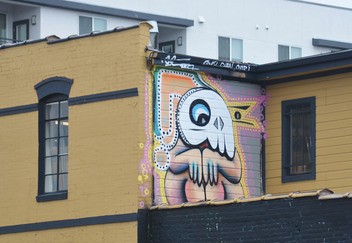 a small mural on an upper storey wall of a small person, naked, sitting with knees up, wearing a large white animal mask