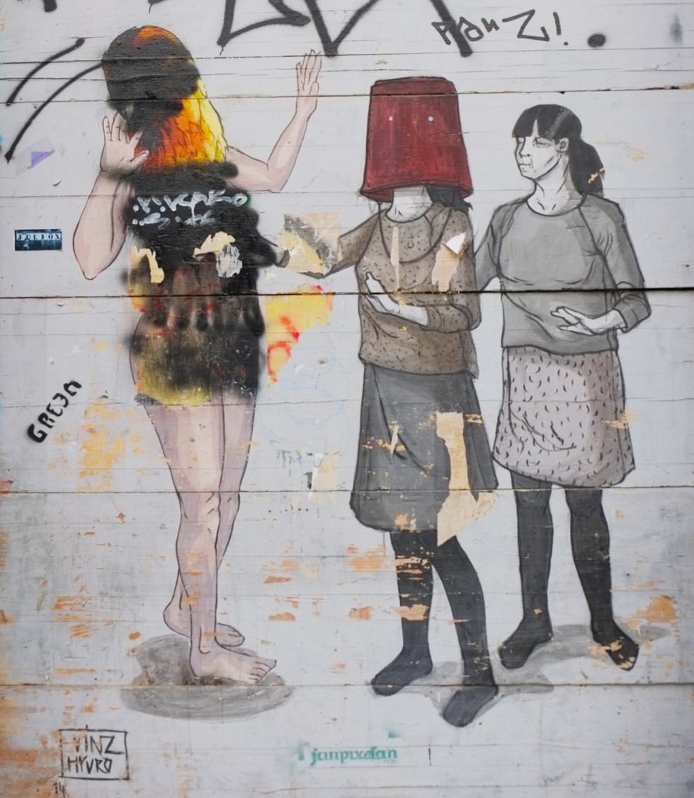 mural on a wall, three women, one in the middle has a red bucket over her head, she is reaching out to the one on the left who has been defaced (port painting). by vynz and hyuro.