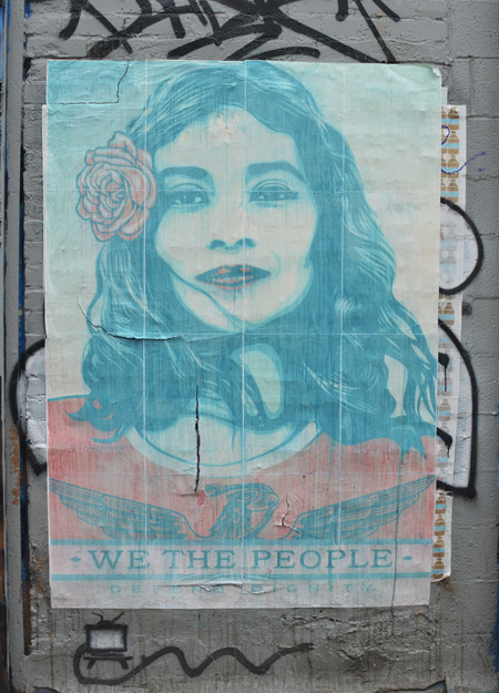 faded poster on an exterior wall, picture of young woman with flower in her hair and the words we the people