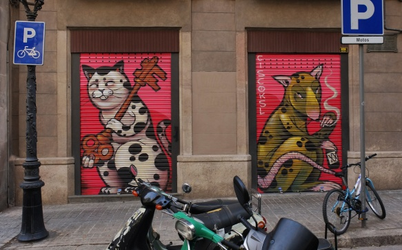 motorcycle in front of two doors with murals. on the left is a cat and on the right is a greenish coloured mouse. both animals fill the door.