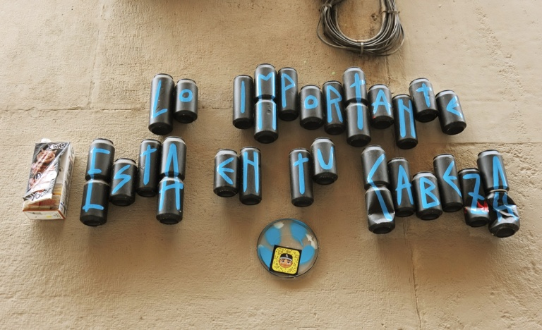 empty cans covered with black and each with a blue letter on them, the cans are put together on a wall so the letters make words.