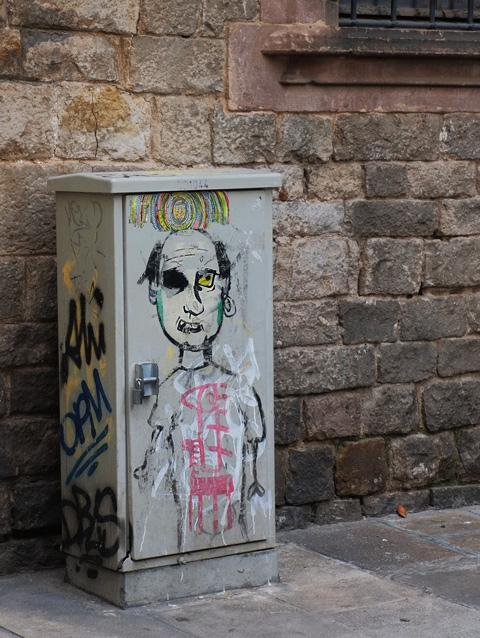 metal utility box on a sidewalk beside a stone wall, drawing of the upper part of a man, in black line drawing.