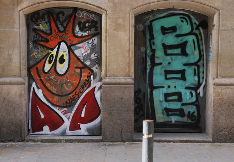 two doors with murals. on the left is goofy faced creature with orange spiky hair and on the right is the word BOB written vertically in large light teal letters.