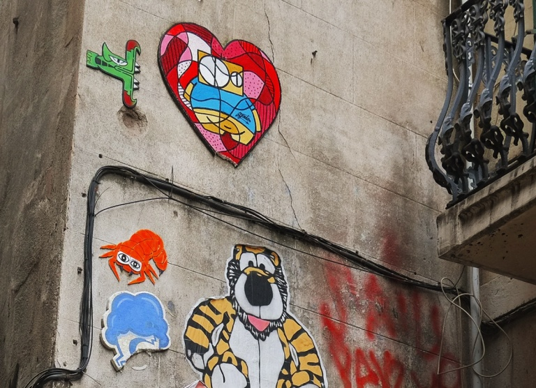 some pasteups and other small pieces of graffiti on a concrete wall. A tiger, a heart, an orange crab.