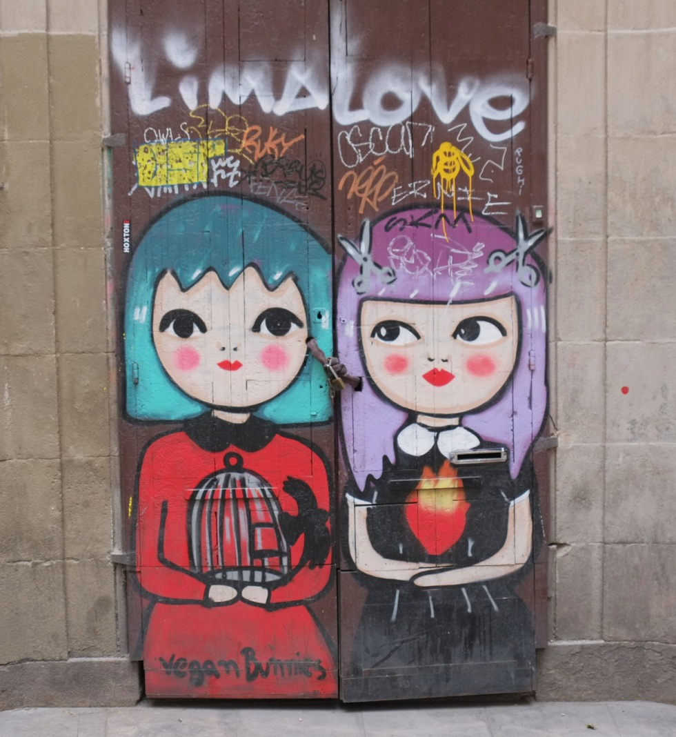 street art painting of two young women on a door, stylized, one with turquoise hair and the other with light purple hair. One with a red dress and holding abird cage that a bird is flying out of. words at bottom say vegan twins. scrawled across the top are the words Lima love.