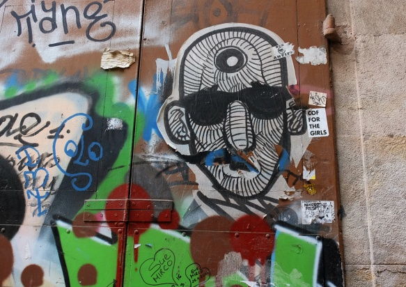 pasteup of a man's face, wearing black sunglasses, also his face is covered with black lines