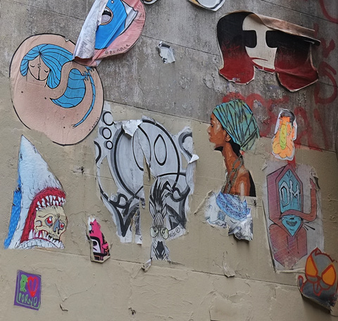 many pasteups on a wall