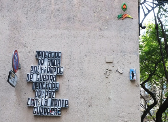 empty cans covered with white, with black letters, one per can, on them. The cans are mounted on a wall in with letters forming words that say mensajes de amor en tiemps de guerra, mensajes de paz con la mente guerrera