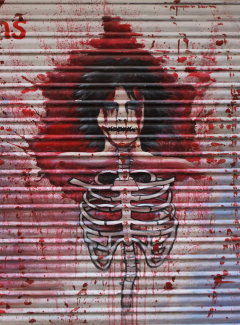 painting on a door of a person's head, with lots of black hair, top of body is just rib cage with lots of red paint that looks like blood splattered all over it
