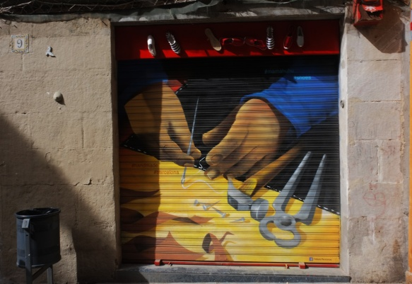 mural on a metal store window covering of a pair of hands working on making shoes