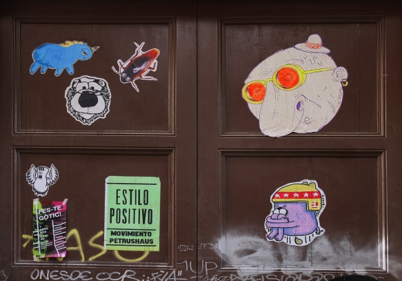 graffiti pasteups on a wooden door