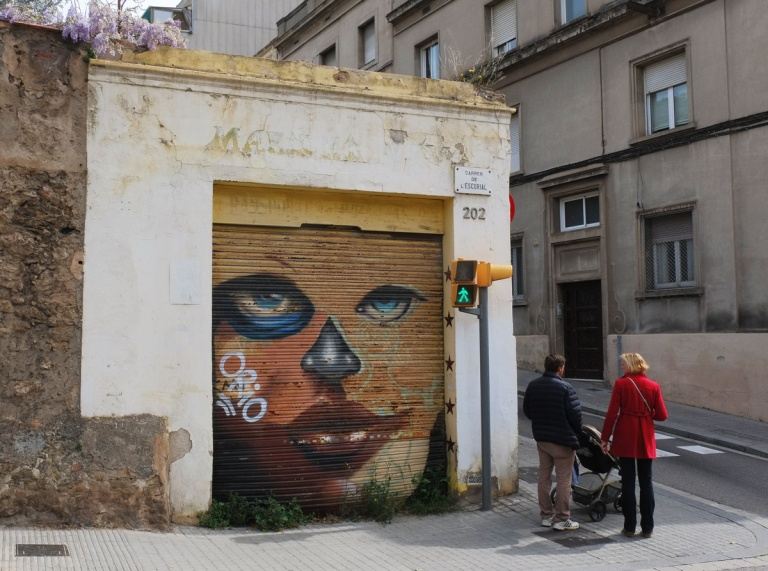 a man and woman pushing a stroller walk past a garage door with a mural of a womans face on it.