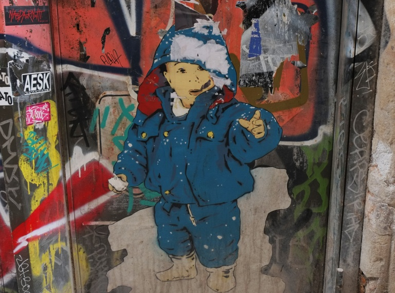 a paste up of a boy in blue snow suit and blue and white hat, he is pointing outwards,