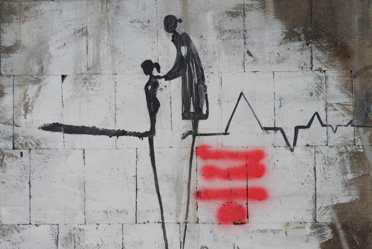 mother and daughter figures in black on a wall, mother is guiding daughter forward, standing on lines that are either heart beats or a chasm