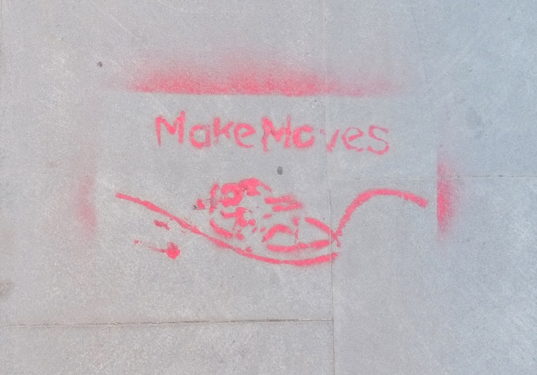 pink stencil written on the sidewalk (pavement) that say Make Moves