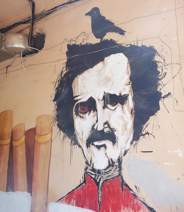 yerevan street art, man's head, black hair and moustache, red shirt, black bird on top of his head
