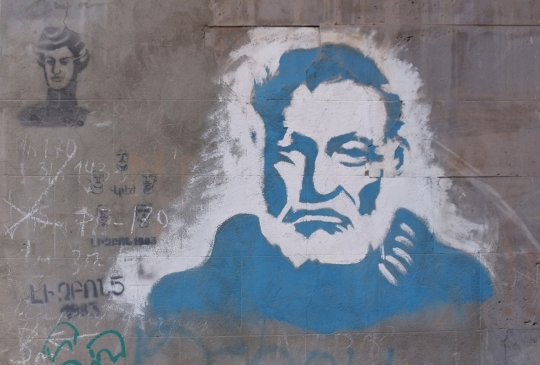 large man in blue and white, older man, small black stencil beside it of another man's head
